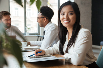 Cheerful young asian businesswoman near colleagues.