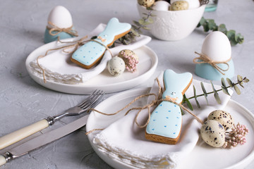 Homemade easter cookies in the shape of  a  funny  rabbit  on white plate. Easter  festive table setting. Holiday decorations.