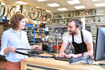 Kundin und Mechaniker in einem Radladen - Beratungsgespräch Reparatur Fahrrad // Customer and mechanic in a bike shop - consultation repair bicycle