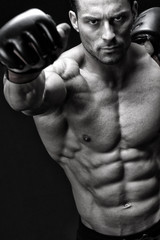 Powerful fighter posing in front of black background
