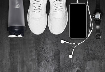 Flat lay shot of Sport equipment. Sneakers, water, earphones and phone on black background.