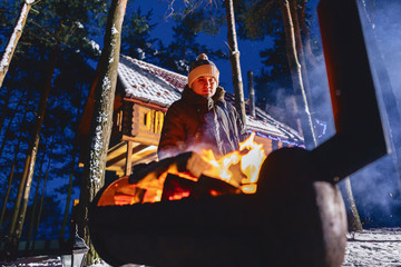 A man fries grilled meat against the background of the cottage in the evening and in the smoke