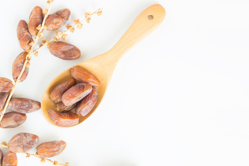 Dates fruit in wooden ladle on white background,Dried date palm fruits top view