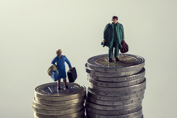 miniature woman and man on piles of euro coins