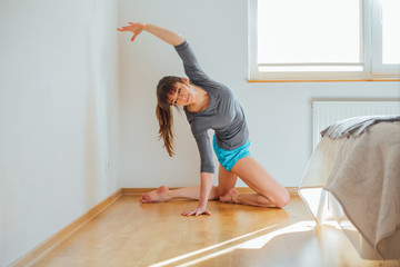 Fitness, home and diet concept - smiling inspiring barefoot woman in sportswear doing yoga or pilates exercise at home in cozy bedroom interior.
