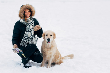 Photo of smiling girl with dog in winter park
