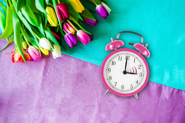 Switch to summer time on alarm clock with tulips from above