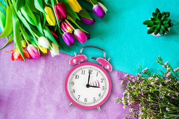 Switch to summer time on alarm clock with tulips and flowers from above