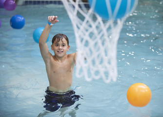 Young boy playing basketball at the indoor water park