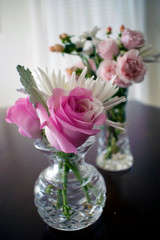 Two crystal vases filled with roses and other small flowers
