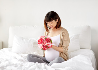 happy asian pregnant woman with flowers in bed