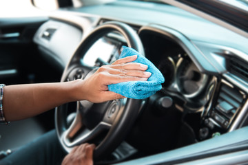 In selective focus of human hand with microfiber cloth cleaning interior car,auto detailing and valeting concept,washing car care interior,blurry light background.