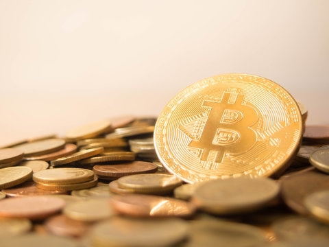 Golden bitcoin cryptocurrency standing out among pile of coins w/ copy space. New digital money and innovative payment network. Financial, business and virtual cryptocurrency concept. Selective focus.