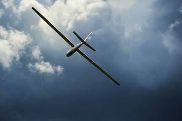 A Glider flying into storm. The glider is a plane that has no engine