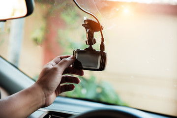 The human hand is touching camera on the car for check system of the recording before use,