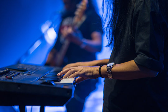 Pianist playing electric piano in concert, music concept.