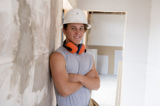 young attractive and confident builder and constructor job trainee learning and working at industrial renovation site blue collar concept