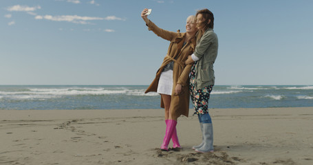 Girls having time and taking selfie on a beach