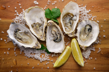 Fresh oysters with lemon on cutting board