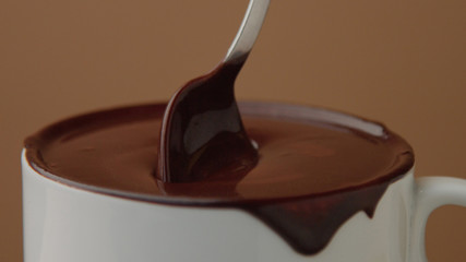 spoon in cup of hot chocolate moving it slowly