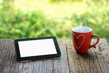 Tablet computer with blank white screen and red cup of coffee on wooden table and blurred nature background