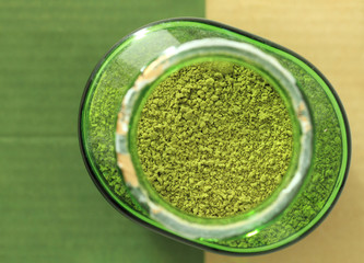 Top view of green tea powder in bottle with brown and green background