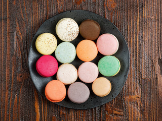 Brightly colored macaroons on a hand-made plate, set on a rustic brown wooden board