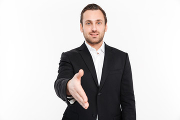Portrait of smiling entrepreneur having stubble wearing black suit offering handshake being welcoming, isolated over white background