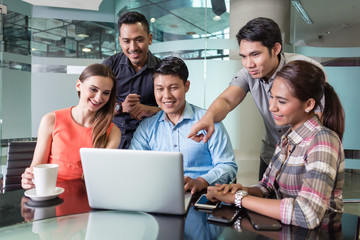 Multi-ethnic team of five cheerful employees smiling while watching a funny video or presentation on laptop in the meeting room of a multinational company