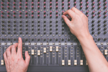 male sound engineer hands working on audio mixing console