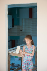 pretty caucasian little girl with brush in house in which there is repair
