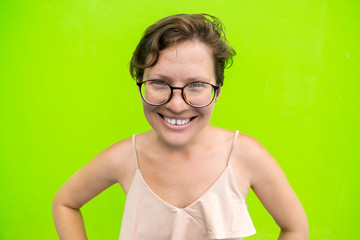 Portrait of an emotional girl in glasses on a green background.