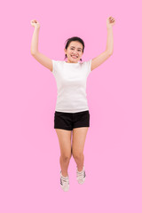 Cute asian woman jumps to cerebrate the winning or success, happy and excite feeling, exercise, white shirt, pink background