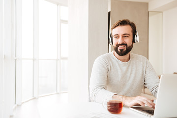 Photo of thoughtful man with short brown hair and beard, listening to music via wireless headphones and chatting on notebook