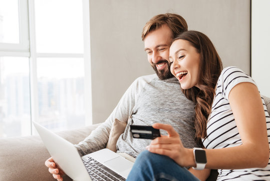Portrait of a laughing young couple shopping online