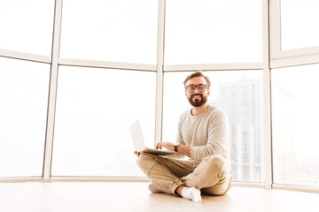 Portrait of a happy man working on laptop computer