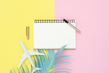 Flat lay design of travel summer concept - Top view mockup of blank paper notebook, pen, pastel coconut leaf and plane on pink yellow pastel color screen. travel in summer on pastel color background.