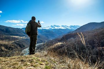 Hiker takes photo of beautiful mountains