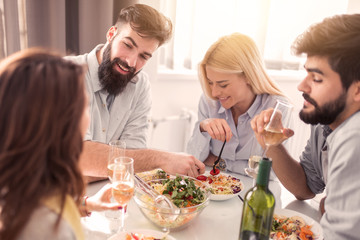 Group of happy young friends eating and having fun at home