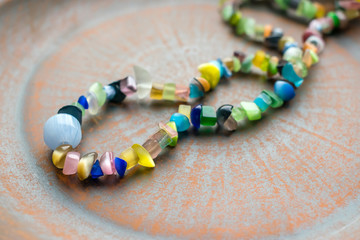 Multi-colored ethnic beads on a brown clay plate. Beads of different bright natural semiprecious stones.Close up Selective focus