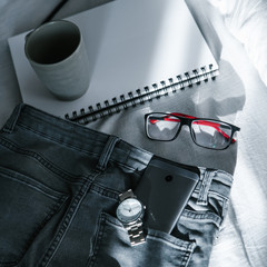 morning concept cup notebook jeans on the bed