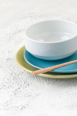 Plates, bowl and wooden spoon on a light gray textural background..