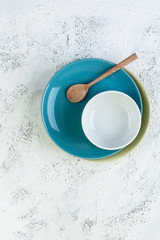 Two plates, a bowl and a wooden spoon on a light gray textural background..