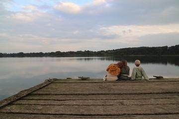 Kinder sitzen am Steg und blicken auf den See