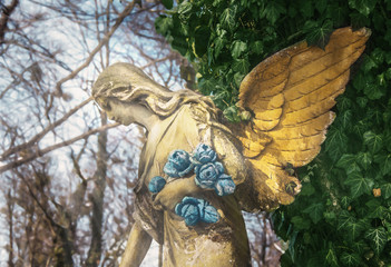 Angel with flowers that animates nature (stone, parable, faith concept)