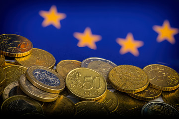 coins of euro and euro cents against the background of the flag of the European Union.  Conceptual.