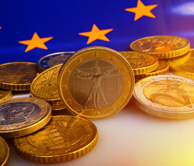 coins of euro and euro cents against the background of the flag of the European Union. Business metaphor.