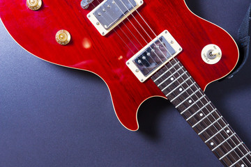 Red electric guitar on black background close-up. Music concept.