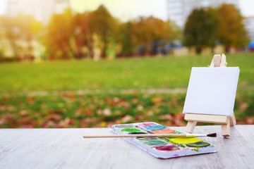 Mini easel, paint and brush on the background of the city park. Draw a landscape in city park. Artist and painting concept.