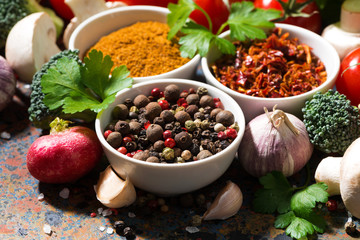assortment of spices and fresh organic vegetables on a dark background, closeup